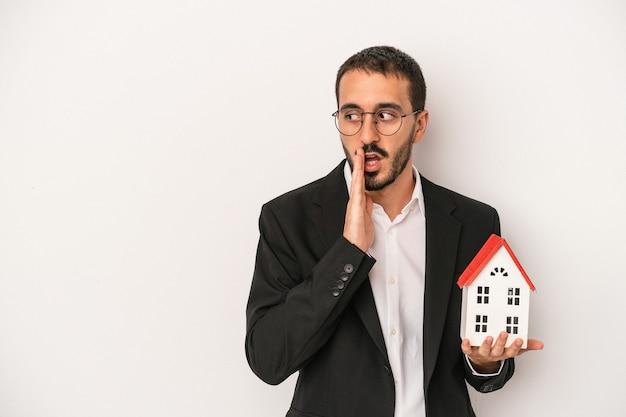 Jovem agente imobiliário segurando uma casa modelo, isolada no fundo branco, contando uma notícia secreta de travagem e olhando para o lado