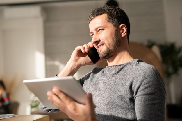 Jovem agente ocupado em roupas casuais olhando pela janela em um dia ensolarado enquanto consulta um cliente no celular e usando o touchpad