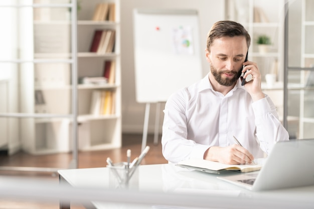 Jovem agente ocupado sentado à mesa no escritório e marcando uma reunião com um dos clientes ao telefone