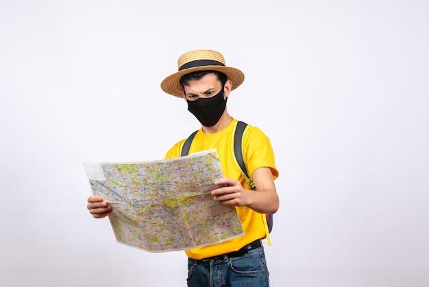 Jovem agitado de frente com camiseta amarela e máscara olhando para o mapa