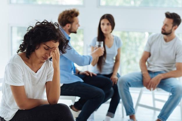 Jovem agradável e infeliz segurando a testa e pensando em todos os problemas enquanto está deprimida