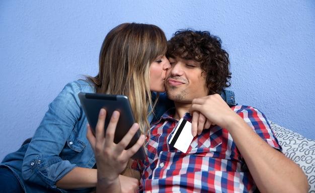 Jovem agradecendo ao marido com um beijo de compra online que ele acabou de fazer com o tablet