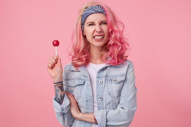 Jovem agressiva linda mulher de cabelos rosa em camisa jeans, segurando um pirulito, olha e mostra os dentes, fica de pé.