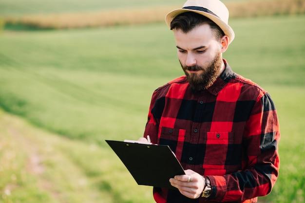 Jovem agricultor barbudo bonito com pé de pasta no campo de trigo verde no início do verão