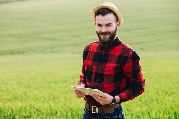 Jovem agricultor barbudo bonito com pé de tablet no campo de trigo no início do verão