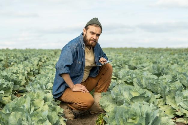 Jovem agricultor confiante com tablet olhando para a câmera