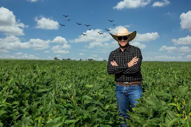 Jovem agricultor de chapéu no campo de soja.