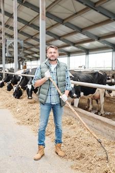 Jovem agricultor de sucesso com um forcado trabalhando em um estábulo dentro de uma grande fazenda de gado leiteiro enquanto olha para a câmera