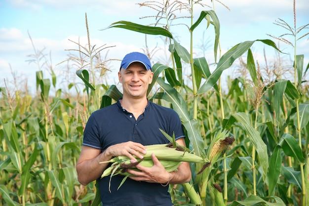 Jovem agricultor em pé no campo durante a colheita
