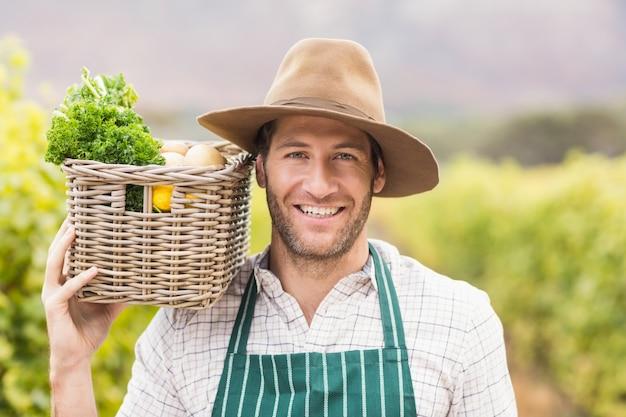 Jovem agricultor feliz segurando uma cesta de legumes