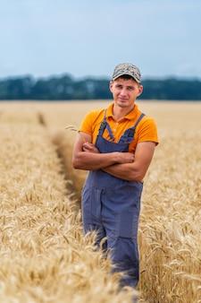 Jovem agricultor fica de mãos cruzadas no campo de ouro. trabalhador profissional da agricultura no trabalho.