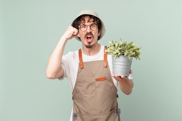 Jovem agricultor gritando agressivamente com uma expressão de raiva