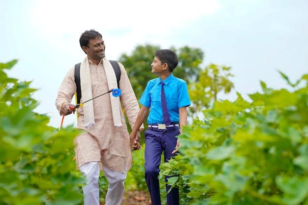 Jovem agricultor indiano com seu filho no campo de agricultura verde.
