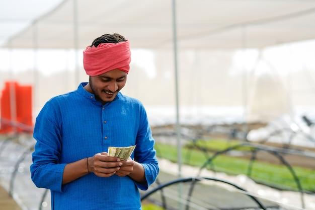 Jovem agricultor indiano contando e mostrando dinheiro na estufa