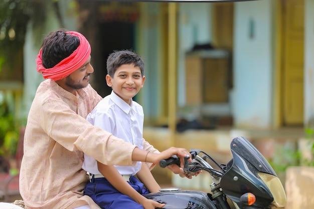 Jovem agricultor indiano deixando seu filho para a escola de bicicleta.