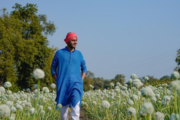 Jovem agricultor indiano em campo de agricultura de cebola