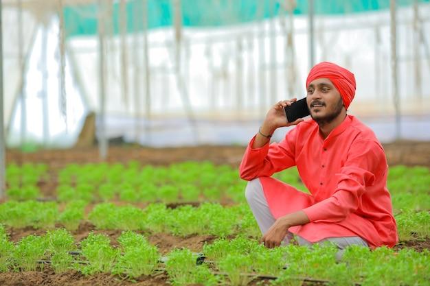 Jovem agricultor indiano falando em smartphone em casa poli