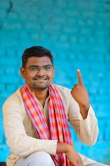 Jovem agricultor indiano mostrando o dedo após a votação. inscrição de voto na índia