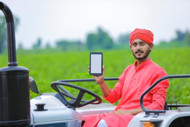 Jovem agricultor indiano mostrando smartphone ou tablet no campo agrícola