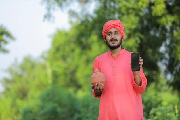 Jovem agricultor indiano segurando o cofrinho de argila e mostrando o telefone inteligente