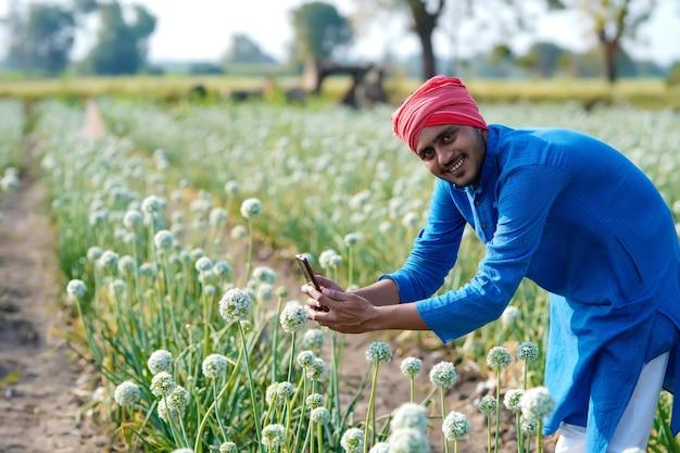Jovem agricultor indiano usando smartphone no campo agrícola