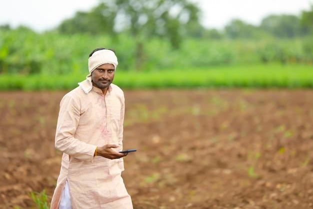 Jovem agricultor indiano usando smartphone no campo de agricultura.