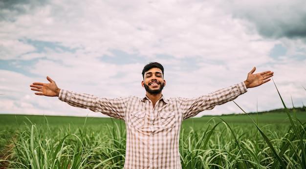 Jovem agricultor latino trabalhando na plantação de cana-de-açúcar. agricultor brasileiro de braços abertos.