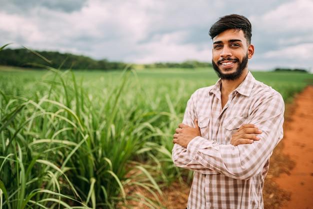 Jovem agricultor latino trabalhando na plantação de cana-de-açúcar. agricultor brasileiro.