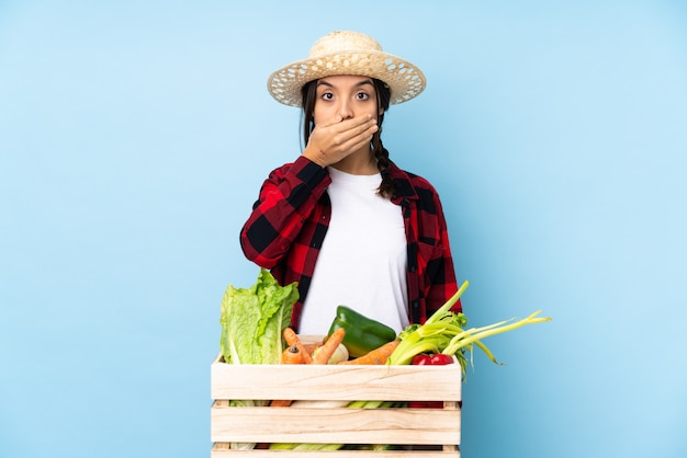Jovem agricultor mulher segurando legumes frescos em uma cesta de madeira, cobrindo a boca com as mãos