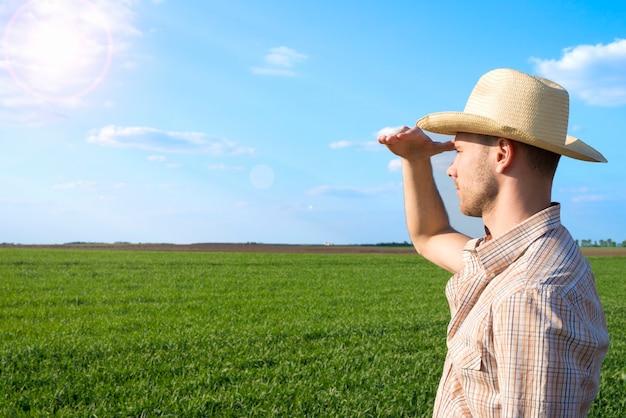 Jovem agricultor no campo observando as colheitas
