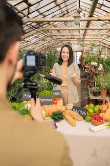 Jovem agricultora asiática positiva em pé à mesa com produtos orgânicos e contando sobre comida saudável enquanto seu colega a filma para vídeo