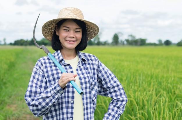 Jovem agricultora asiática sorrindo e segurando uma ferramenta em uma fazenda de arroz verde