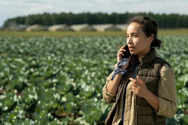 Jovem agricultora falando no celular contra a plantação