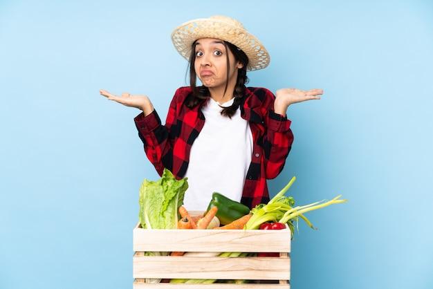 Jovem agricultora mulher segurando legumes frescos em uma cesta de madeira fazendo gesto de dúvida