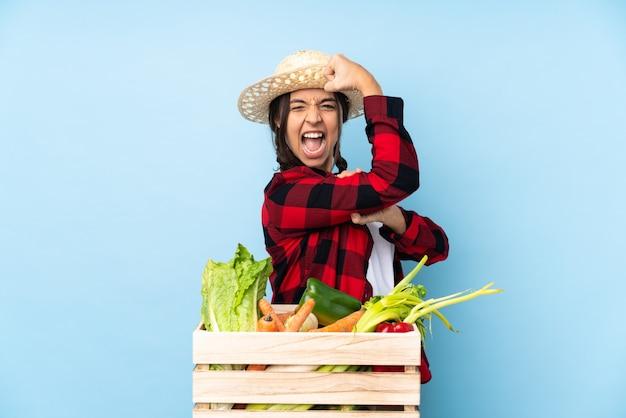 Jovem agricultora mulher segurando legumes frescos em uma cesta de madeira fazendo um gesto forte