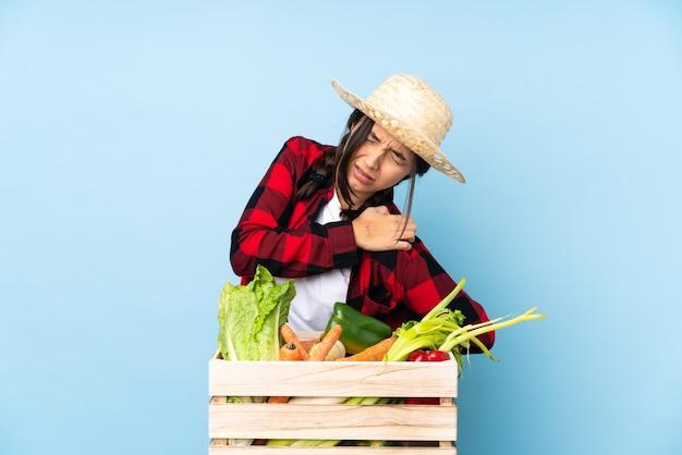 Jovem agricultora mulher segurando legumes frescos em uma cesta de madeira, sofrendo de dor no ombro por ter feito um esforço