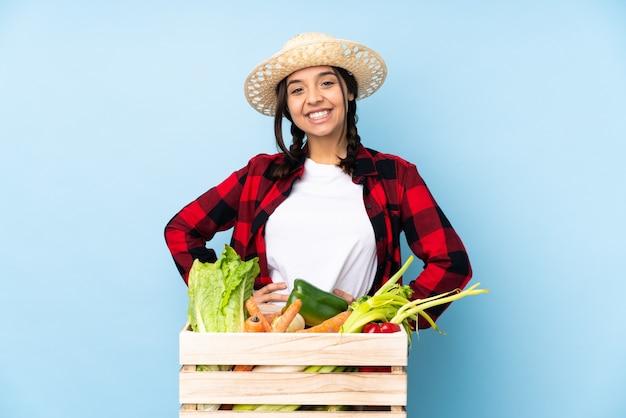 Jovem agricultora mulher segurando legumes frescos em uma cesta de madeira