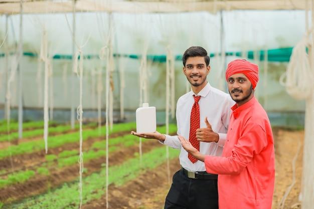 Jovem agrônomo e fazendeiro indiano mostrando garrafa na estufa