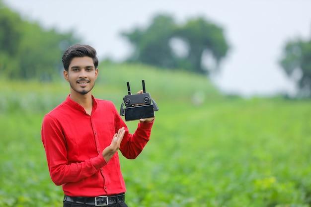 Jovem agrônomo indiano controlando drone voador em campo agrícola