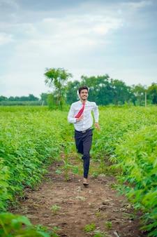 Jovem agrônomo indiano correndo em um campo de feijão bóer