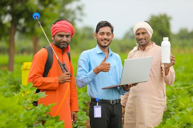 Jovem agrônomo indiano dando um frasco de fertilizante líquido ao agricultor e aparecendo no campo de agricultura.