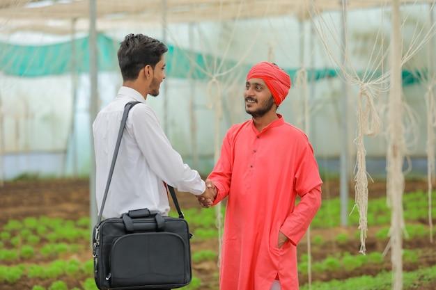 Jovem agrônomo indiano discute com agricultor em estufa