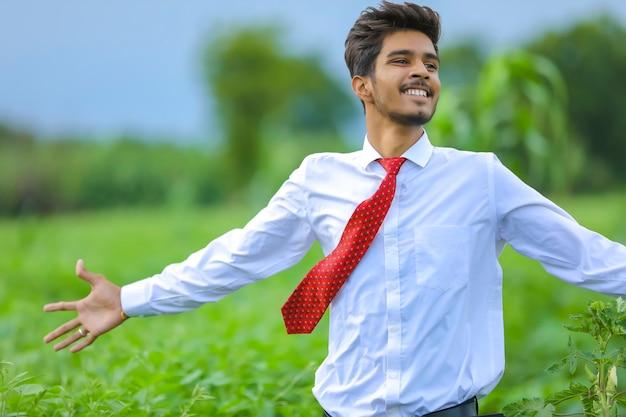 Jovem agrônomo indiano em pé no campo apontando a direção