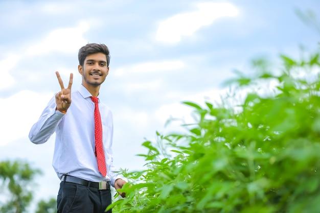 Jovem agrônomo indiano em pé no campo fazendo sinal de vitória