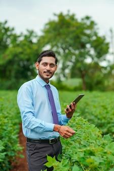 Jovem agrônomo indiano ou oficial usando tablet no campo de agricultura.