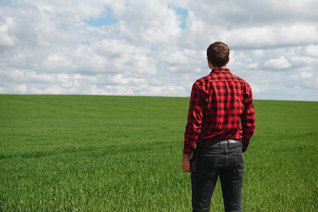 Jovem agrônomo mantém computador tablet touch pad no campo de trigo verde. conceito de agronegócio