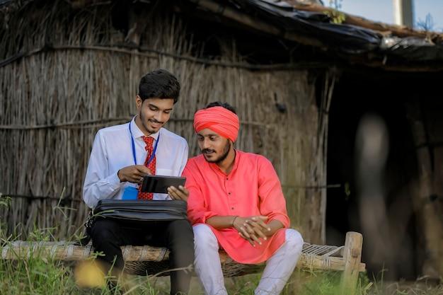 Jovem agrônomo ou banqueiro indiano mostrando algumas informações ao agricultor no smartphone