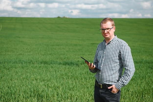 Jovem agrônomo segura computador tablet touch pad em campo de trigo verde