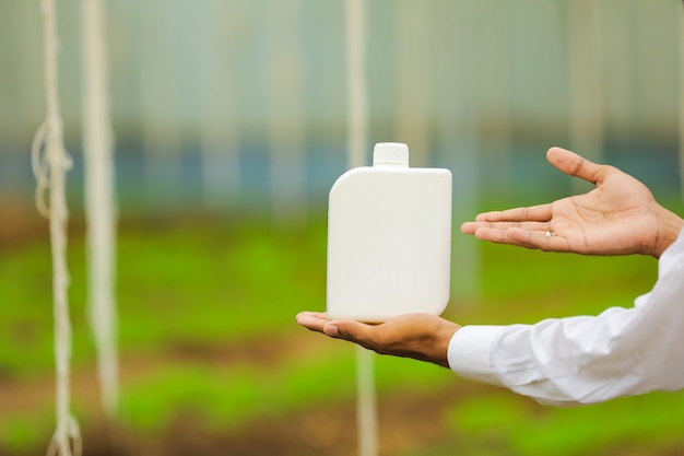 Jovem agrônomo segurando uma garrafa na mão na estufa