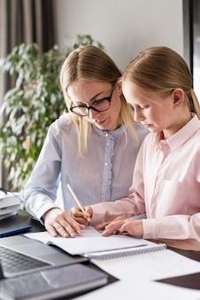 Jovem, ajudando a garota com lição de casa